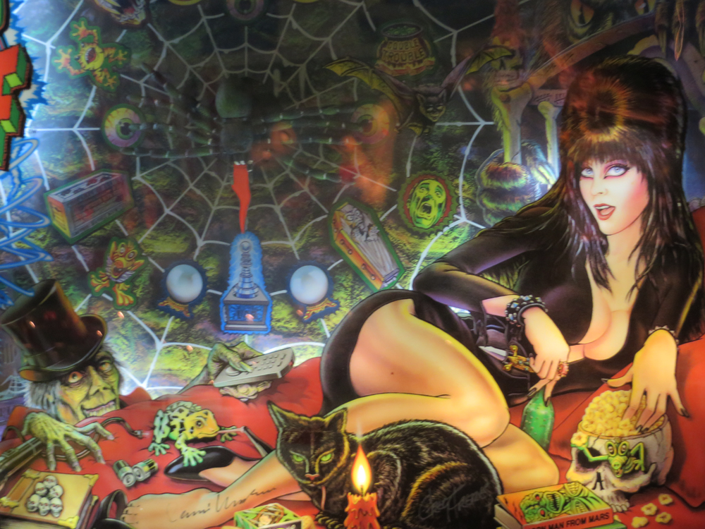 Welcome to Deviation Obligatoire's exploration of Boobs in Pinball. I can't think of anyone better to welcome you than the Mistress of the Dark herself. Have you ever thought about what her head is shaped like under there, considering that front-and-center part? I didn't until I was taking this picture. Now you can too. Fun fact: there are multiple Elvira-themed pinball machines. I love earth sometimes.