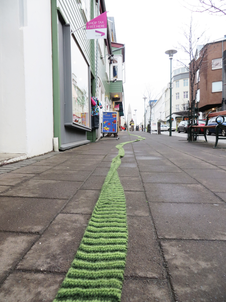 a striped green scarf unrolled on the sidewalk of brautarholt in reykjavik