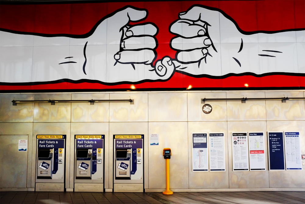 Mural of two interlinked hands on the wall at the Capitol Hill Light Rail Station