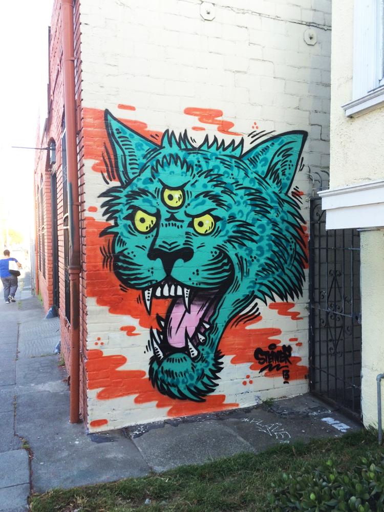 Turquoise three-eyed cat graffiti in Oakland