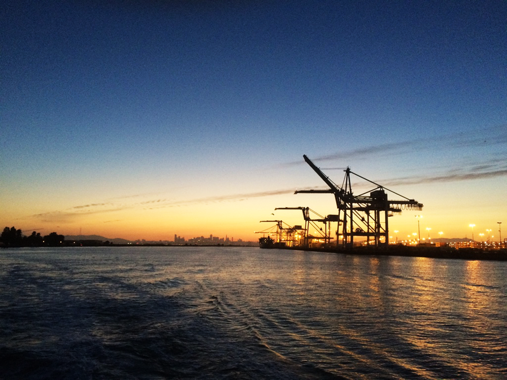 The cranes of Oakland's harbor, magnificent sunset behind