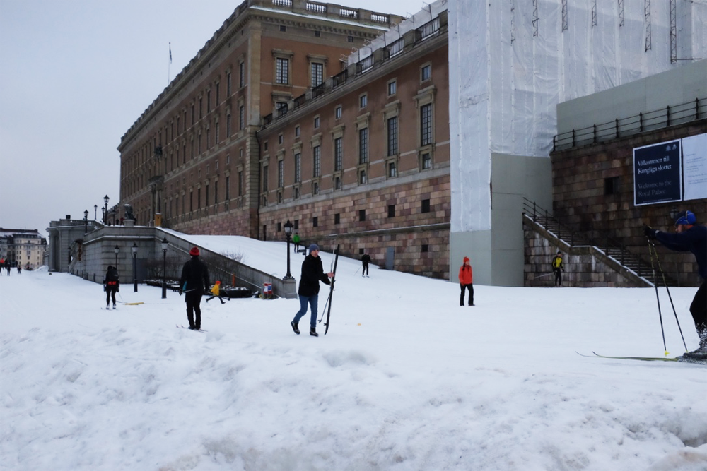 A snowy slope and skiers behind Stockholm's Royal Palace