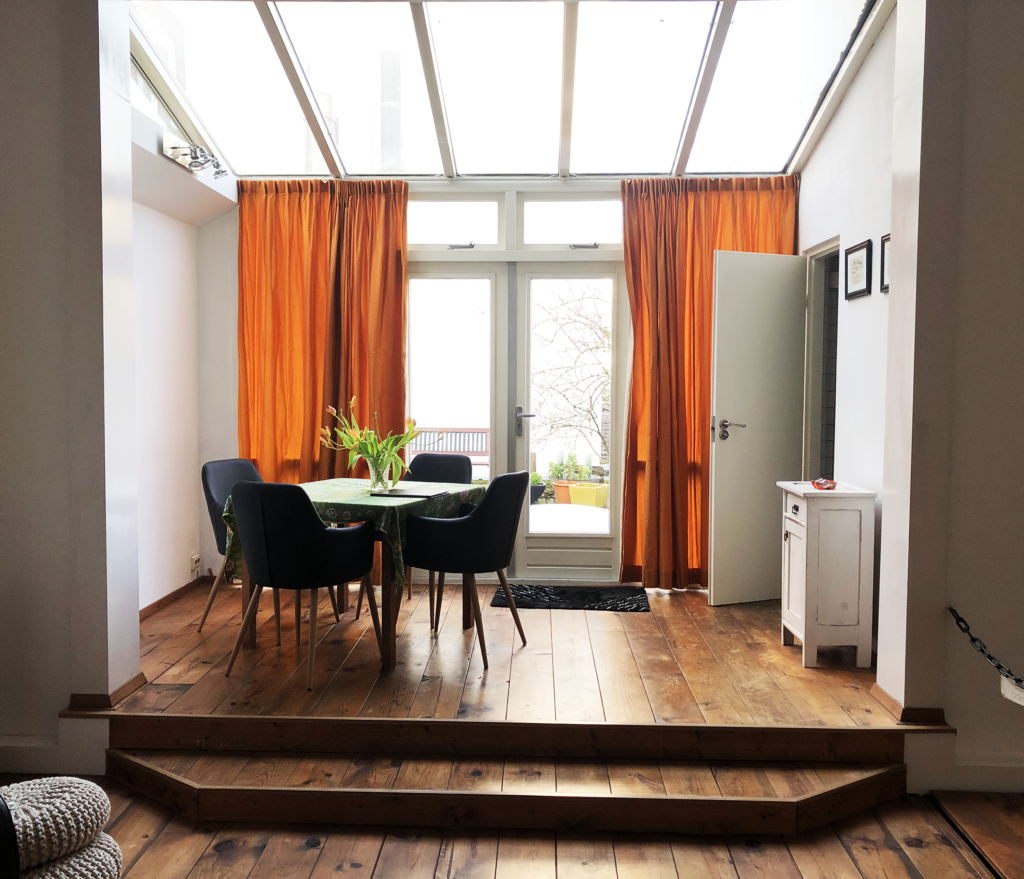 A photo of a table and chairs inside an apartment with a broad skylight and orange curtains framing sliding doors that lead to a patio