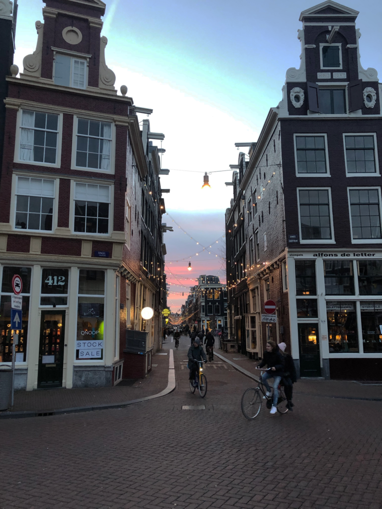 A photo of leaning Amsterdam canal houses on either side of a narrow cobblestone street with cyclists, in front of a pink-and-blue sunset-streaked sky