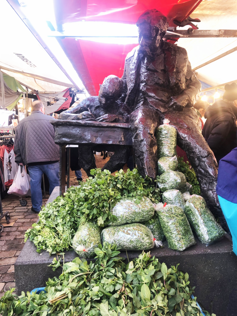 A photo of a modern statue of a man helping a boy with work at a desk, surrounded by bags of parsley in a bustling farmers market