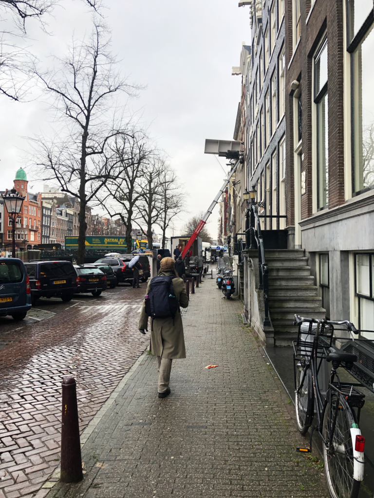 A photo of a man walking down a canal street in Amsterdam, toward a truck with an extended ladder for lifting furniture into open windows