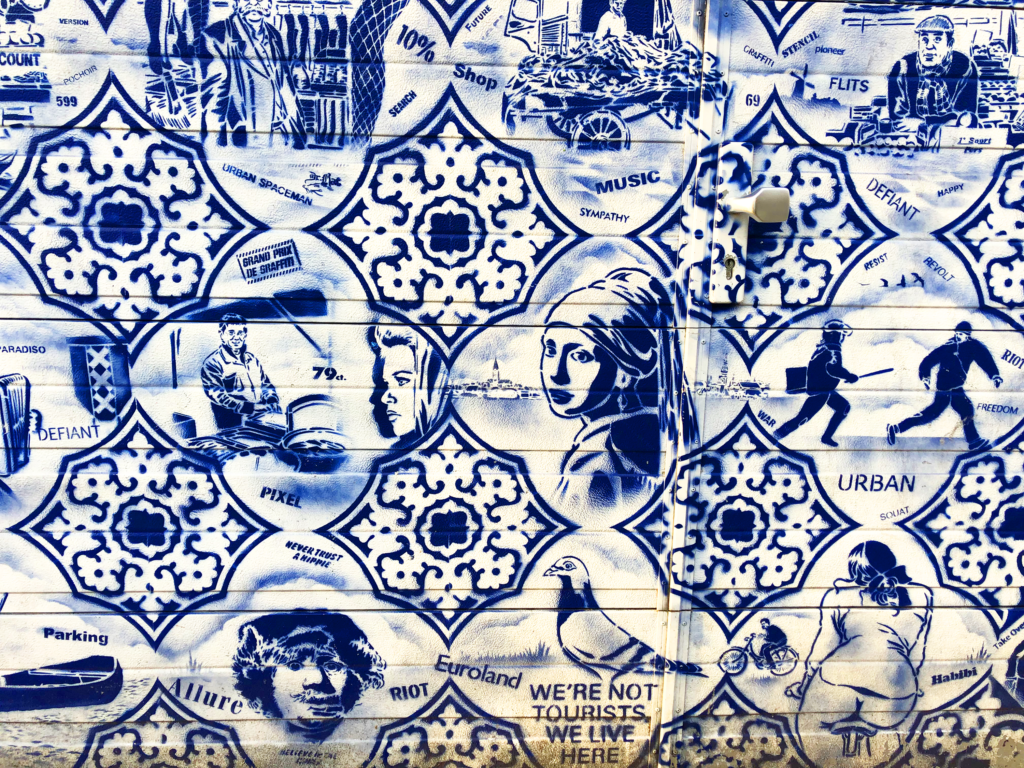 A photo of blue-and-white stenciled graffiti with a pigeon, a woman on a bike, the Girl with Pearl Earring, and other scenes from Amsterdam