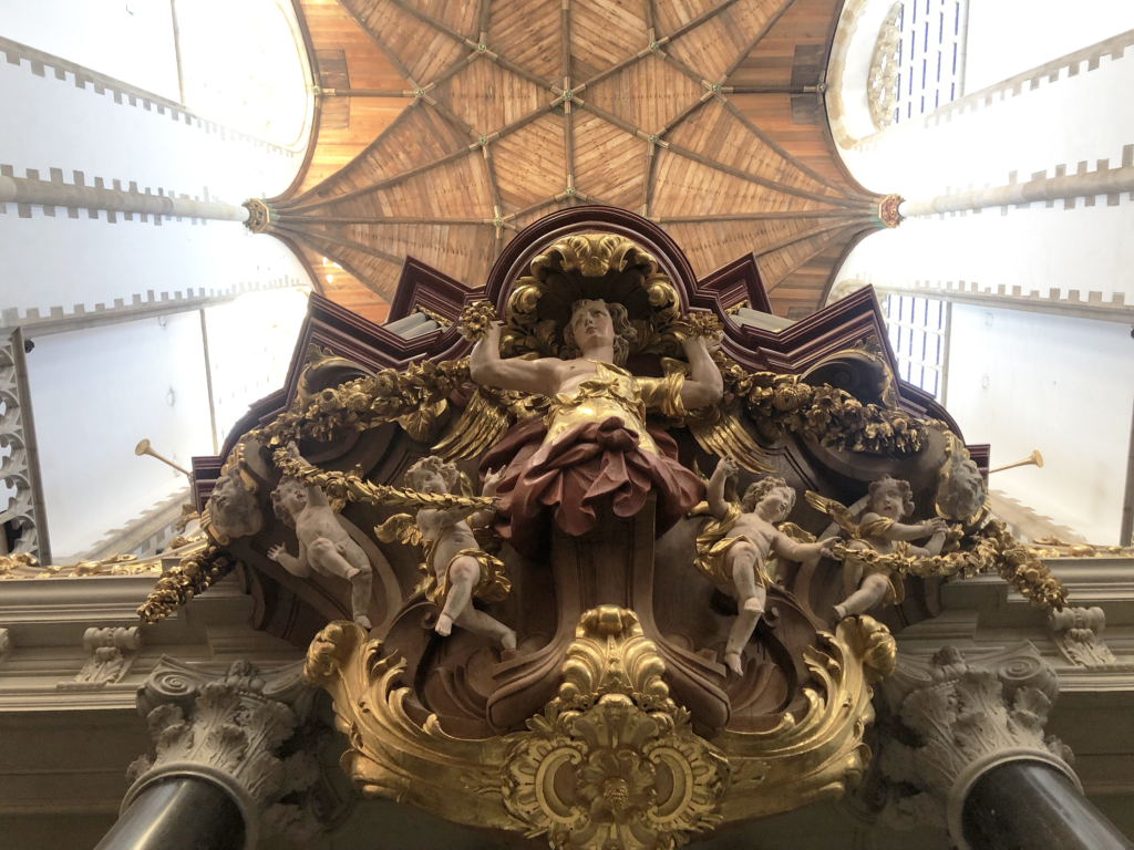 A photo looking up at painted wood carvings of cherubs and gilded garlands, below a ceiling made of light-brown wooden rafters