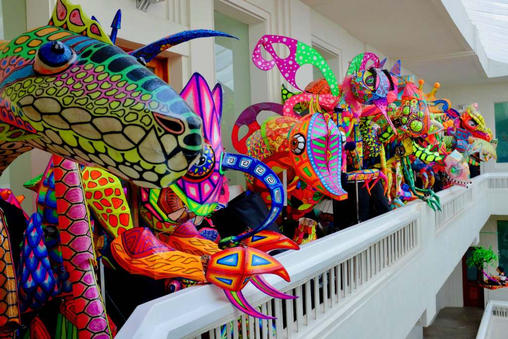 Several human-sized brightly colored alebrije sculptures made with paper, gathered on a white balcony at the Museo Artes Populares