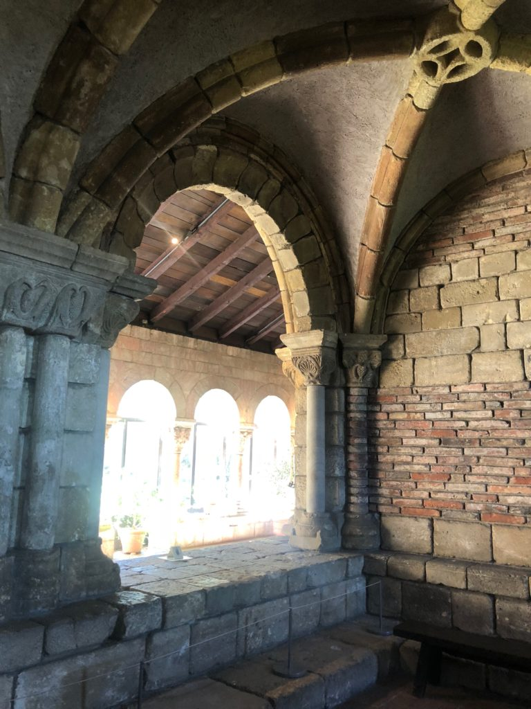 Brick walls and arches, light shining through behind them, at the Cloisters in New York