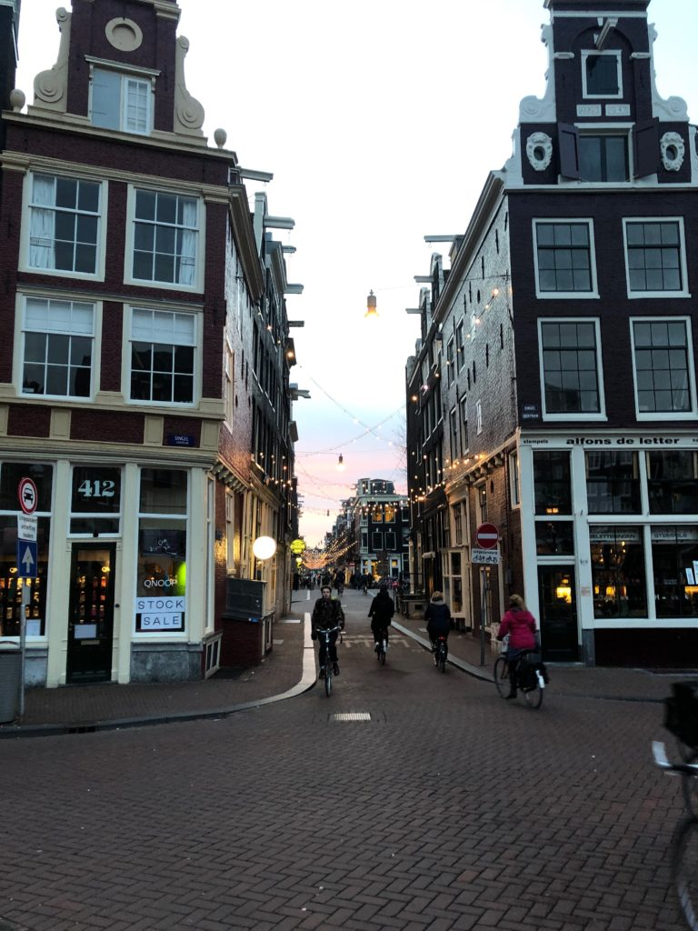 Townhouses of central Amsterdam with streaks of blue-and-pinky dusky sky behind them