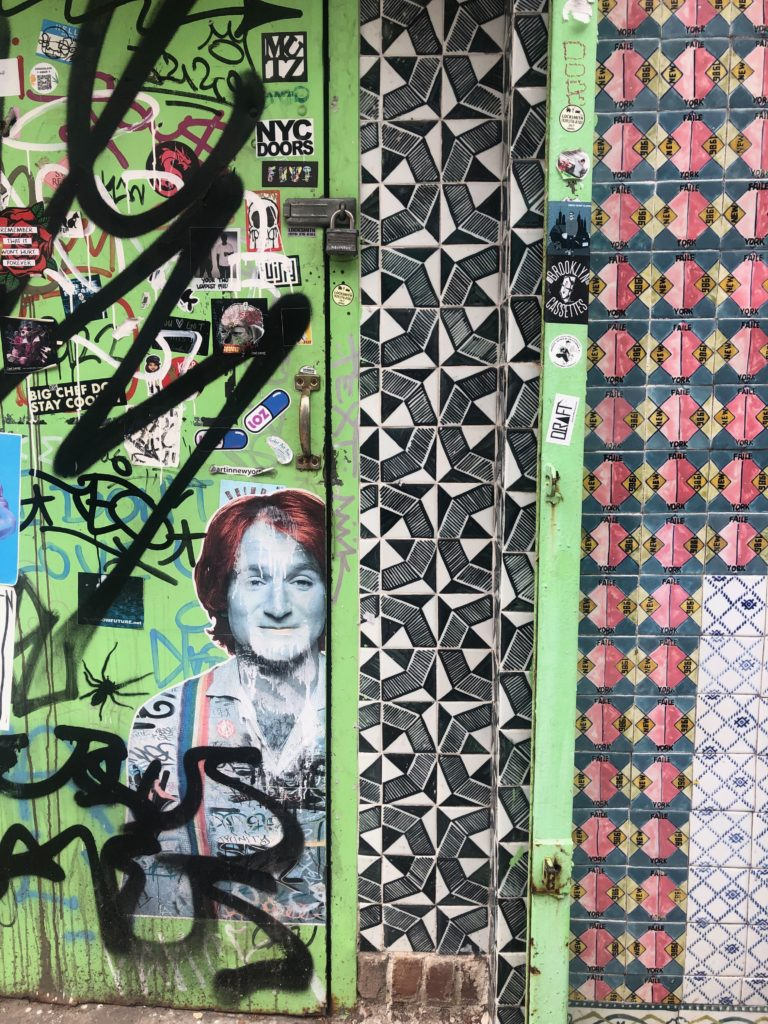 a stencil of Robin Williams and patterned tile on a wall